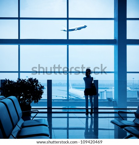 girl at the airport window and flight departure - stock photo