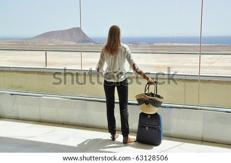 Girl at the airport window looking to the Atlantic ocean. Tenerife, Canaries - stock photo