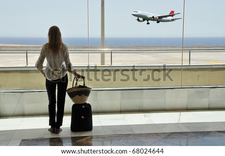 Girl at the airport window looking to the ocean - stock photo