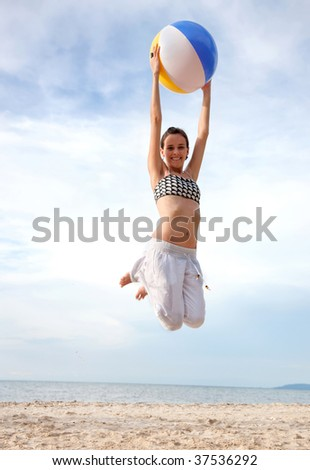 Girl at the beach jumping with a ball