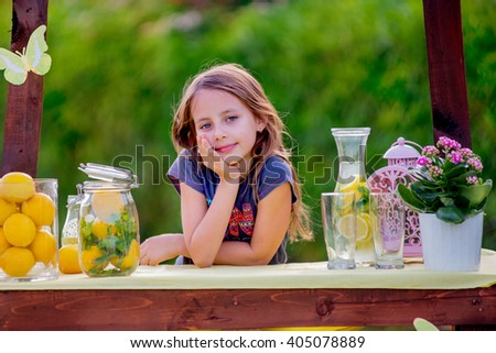 Girl at the lemonade stand is waiting for customers - stock photo