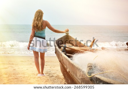 Girl at the old fishing boat looking to the ocean. Rajbag beach of South Goa, India - stock photo