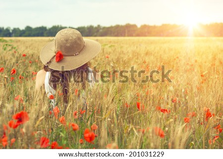 girl at the poppies field  - stock photo