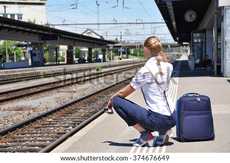 Girl at the railway station waiting for a train