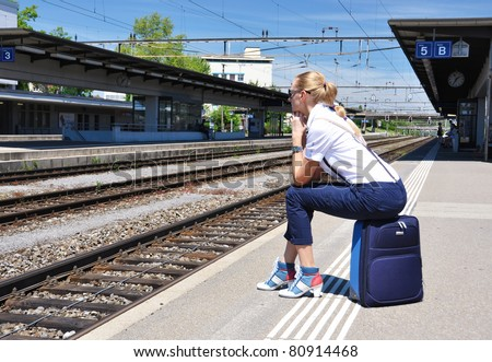 Girl at the railway station waiting for a train - stock photo