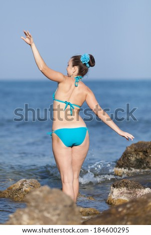 Girl at the sea. Young woman in blue swimwear on rocky seashore, rear view