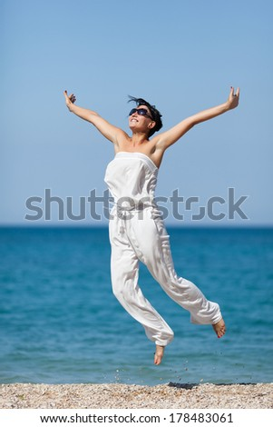 Girl at the sea. Young woman in jumpsuit jumps on seashore - stock photo