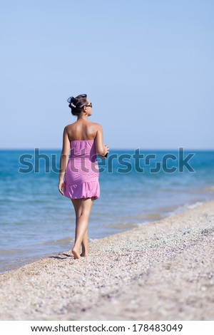 Girl at the sea. Young woman in sundress walks along the seashore - stock photo
