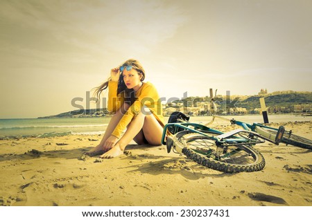 Girl at the seaside and her bike  - stock photo