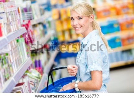 Girl at the shop choosing cosmetics among the great variety of products. Concept of consumerism, retail and purchase - stock photo