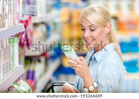 Girl at the shopping mall choosing cosmetics among the great variety of products. Concept of consumerism, retail and purchase - stock photo