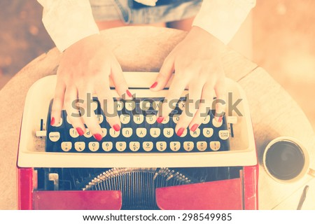 Girl at the table typing on a typewriter, vintage photo effect - stock photo
