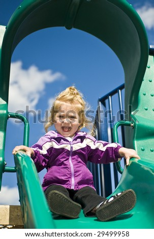 Girl at the top of the slide - stock photo