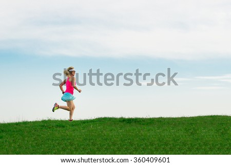 Girl athlete runs in the meadow in colored clothing