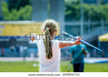girl athlete tries throwing javelin. view from back. summer competition at stadium - stock photo
