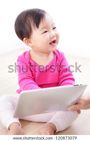 Girl baby happy play game with tablet PC. asian child smile look her mother - stock photo