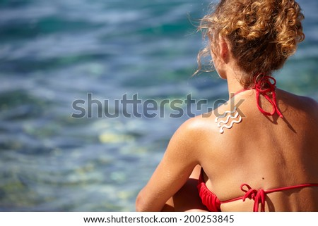 girl back with sunburn and wave of sun lotion  - stock photo