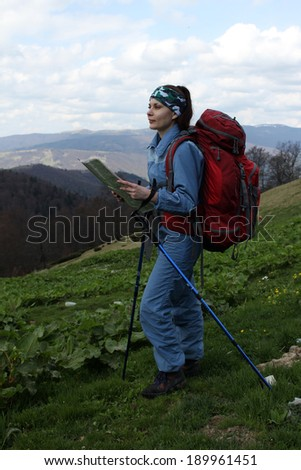 girl backpacker on top of a mountain with map