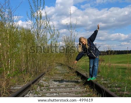 Girl  balancing on rails - stock photo
