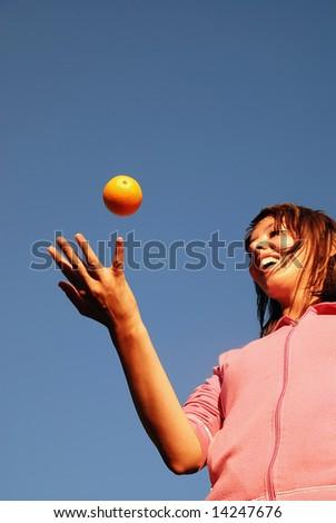 girl balancing orange in air - stock photo