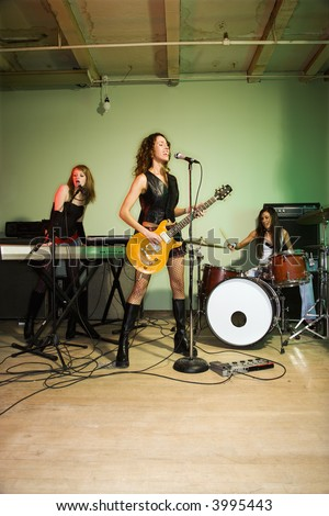 Girl band playing their instruments. - stock photo