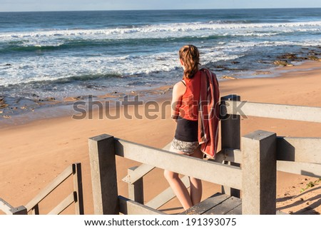 Girl Beach Ocean Stairs Teen  girls stand on walkway stairs overlooking beach ocean waves and coastline early morning. - stock photo