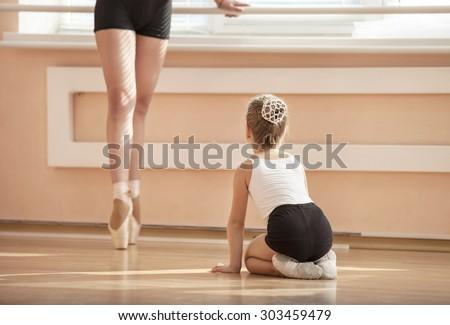 Girl beginner watching classmate standing en pointe in ballet dancing class - stock photo
