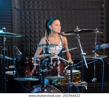Girl behind drum-type installation in a professional recording studio - stock photo