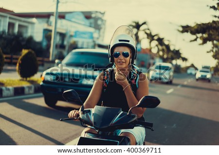 girl behind the wheel scooter . Girl with dreadlocks , bright hippie appearance on a motorbike in Asia.  - stock photo