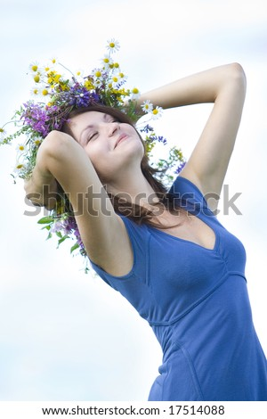 girl bending and smiling with wreath - stock photo