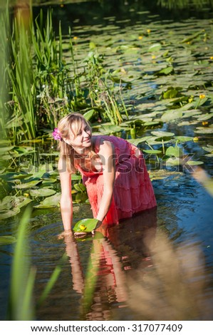 girl bent toward the water lily flower
