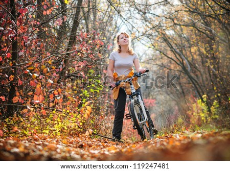girl biking in autumn forest
