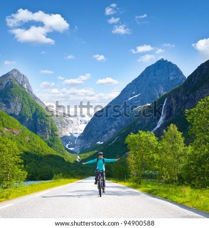 Girl biking in high mountains in Norway - stock photo