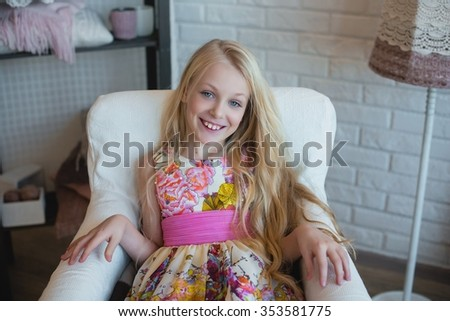 Girl blonde with long hair sitting in a chair and smiling, decoration, decor, lifestyle, family, family values
