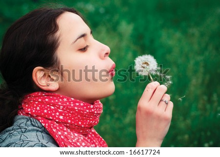 girl blow on Dandelion against a background grass
