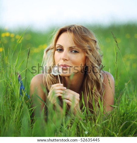 girl blow on dandelion on green field - stock photo