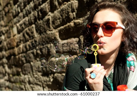 Girl blowing bubbles at the wall