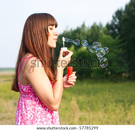 Girl blowing bubbles of soap in sunny weather