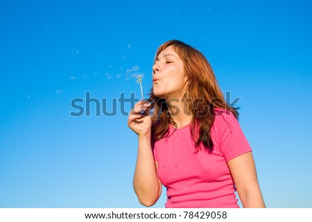 girl blowing dandelion - stock photo