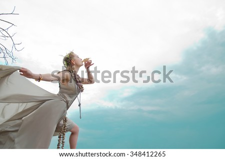 girl blowing into sink, gown of silver parachute silk necklace of shells and pearl + gold jewelry. Wind storm. An allusion to the Scandinavian and Celtic mythology. - stock photo