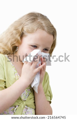 Girl blowing nose into tissue
