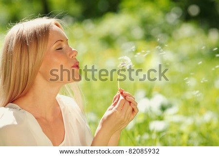 girl blowing on a dandelion - stock photo