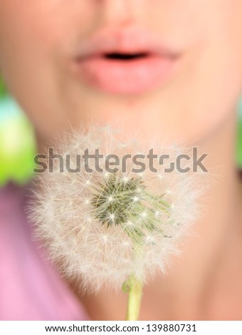 Girl blowing on dandelion close up - stock photo