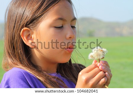 Girl blowing on dandelions and making a wish. - stock photo