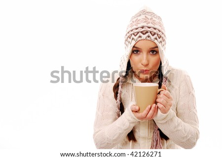 Girl blowing on hot drink dressed in winter clothing - stock photo