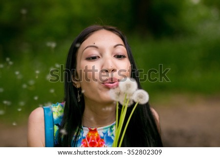 Girl blowing on white dandelion in park