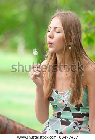 Girl blowing on white dandelion in summer park