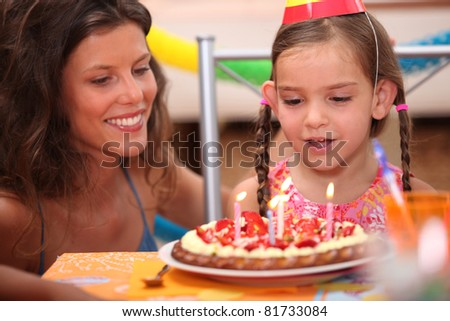 Girl blowing out candles - stock photo