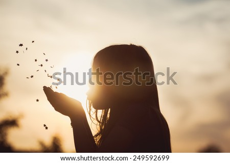 Girl blowing stars at sunset. - stock photo