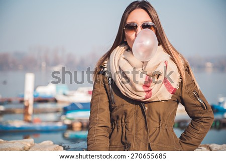 Girl blows big bubble from bubble gum - stock photo